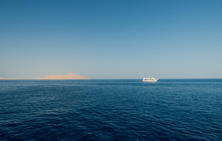 Boat in blue sea at island on horizon background