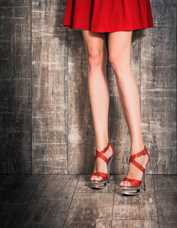 sexy young caucasian woman legs in high heels on a wooden background Zdjęcie Seryjne
