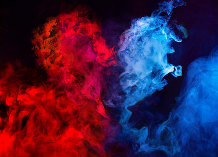 abstract shapes of red and blue smoke in heart shape at dark background Banco de Imagens