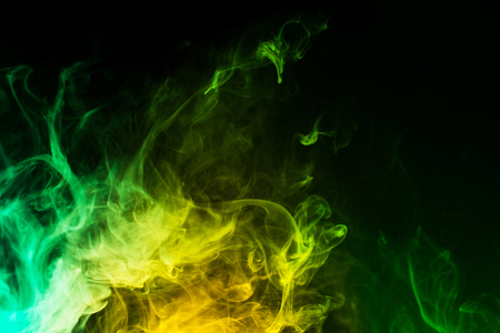 abstract yellow and green smoke on black background
