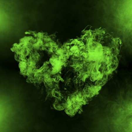 heart shape from green smoke isolated on black background