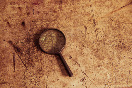 old dusty magnifier on scratched wooden vintage surface