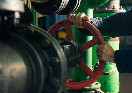 man holding red valves in technical room Standard-Bild