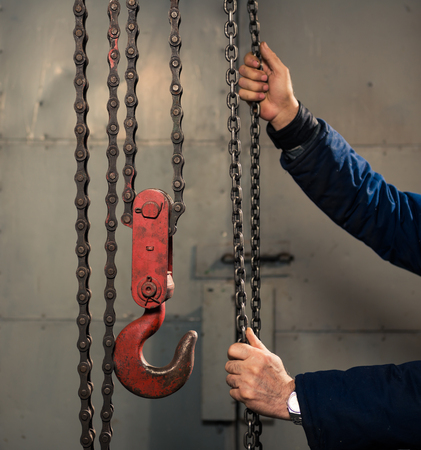 senior man holding metallic chain