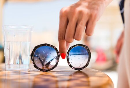 woman taking sunglasses from summer pool table