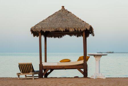 sunbed with table on a sand beach Standard-Bild