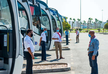 Egypt, Hurghada - 07/11/2020. tour guides in protective masks waiting for tourists at buss station near airport