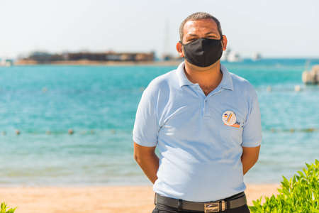 Egypt, Hurghada - 07/15/2020. friendly portrait of egyptian hotel staff in pritective face mask at summer sea beach background Editorial