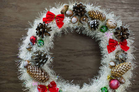 beautiful white Christmas wreath on brown wooden background