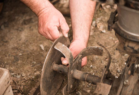 farmer prepares plowing mechanism for work on farmland soil in spring
