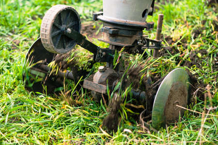 plowing machine working with soil at springtime farmland Standard-Bild