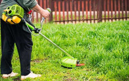 farmer working with grass-cutter on spring farmland soil Standard-Bild