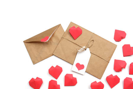 Envelope from craft paper with red heart and gift wrapped in brown craft paper, tied with twine with a bow, with label with heart, surrounded by several handmade red 3D paper hearts on white background isolated.
