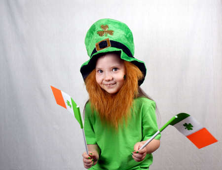 Saint Patricks Day holiday. Portrait of adorable smiling girl with decorative red beard, green clover leaf on her cheek and leprechaun hat, holds flags of Ireland in her hands