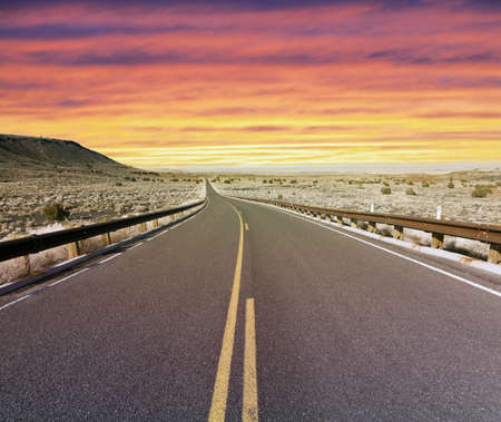 Desert highway at sunset Stock Photo