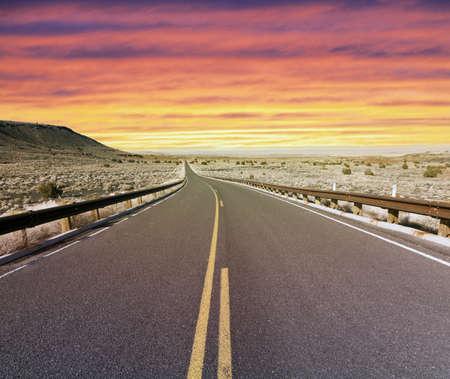 Desert highway at sunset Standard-Bild