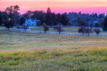 rancho: Puesta de sol sobre una granja de caballos Foto de archivo
