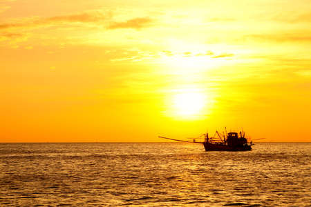 Fishing boat in the ocean at sunset photo