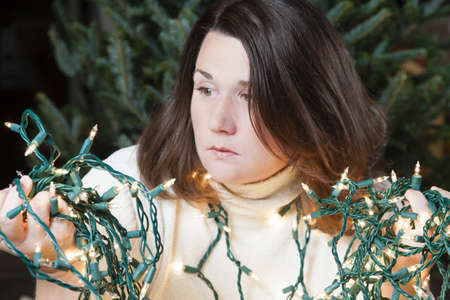 Young woman sitting next to Christmas tree holding entangled string of lights