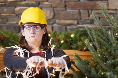 home safety: Young woman wearing hardhat and safety glasses plugging in Christmas tree lights Stock Photo