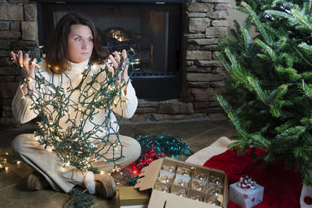 cable tangle: Young woman sitting next to Christmas tree holding entangled string of lights