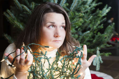 woe: Young woman sitting next to Christmas tree holding entangled string of lights