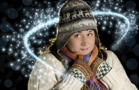 Young woman in warm clothing surrounded by sparkling flurries photo
