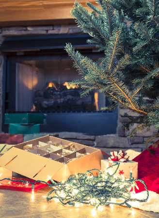 fireplace home: Image of a bare Christmas tree with boxes of ornaments next to it