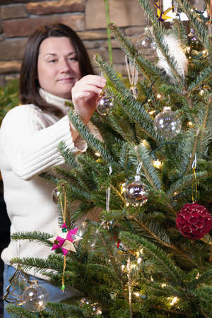 decorating christmas tree: Young woman is decorating Christmas tree at home