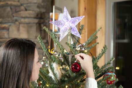 Young woman is decorating Christmas tree at home photo