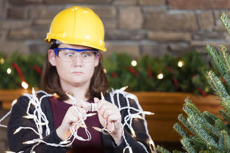 safety: Young woman wearing hardhat and safety glasses plugging in Christmas tree lights Stock Photo