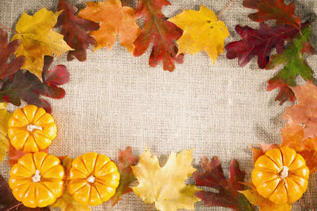 fall themed background of burlap dry leaves and pumpkins stock
