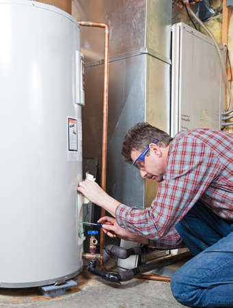 electric utility: Water heater maintenance by the technician Stock Photo
