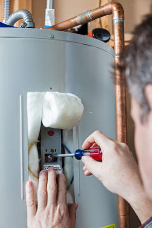 plumbing: Man doing Water heater maintenance Stock Photo