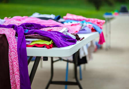 Clothes laid out on a table at a garage sale photo