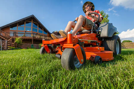 A man is mowing backyard on a riding zero turn lawnmower Imagens