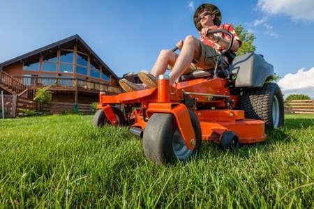 A man is mowing backyard on a riding zero turn lawnmower Stockfoto