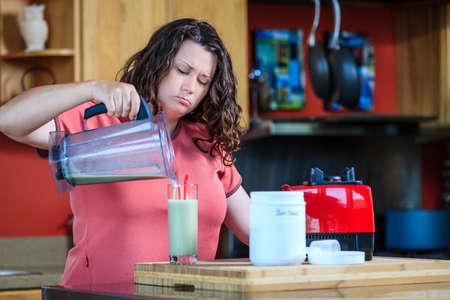 weerzinwekkend: Vrouw gieten water in het glas na het maken van Diet Shake Stockfoto