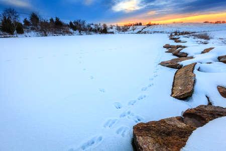 huellas de animales: Escena de la puesta en un lago congelado en el centro de Kentucky