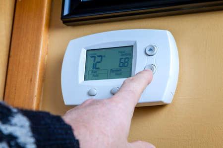 ahorro energetico: Finger Ajuste el termostato en casa Foto de archivo