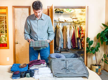 packing suitcase: A man is packing his suitcase for a trip