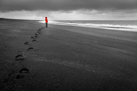 woman alone: Icelandic coast, black sand beach Stock Photo