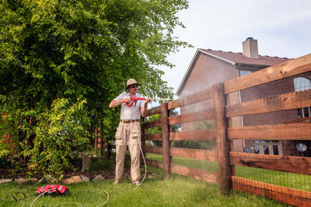 A man is cleaning wooden fence with electric power washer Stockfoto