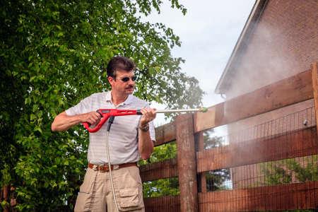 한 남자가 전기 와셔로 나무 울타리를 청소하고있다. 스톡 콘텐츠