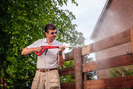 A man is cleaning wooden fence with electric power washer Archivio Fotografico