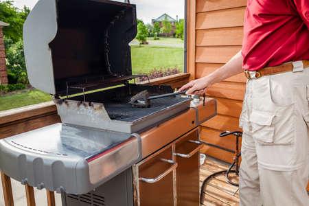 Een man is het reinigen van de grill roosters met een staalborstel