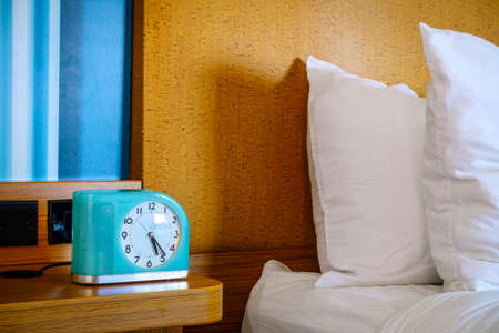 bedside: Bedside table with alarm clock at a hotel Stock Photo
