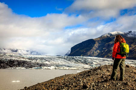 terminus: Caminante en la orilla de la laguna Fjallsarlon en una terminal del glaciar en el sur de Islandia Foto de archivo