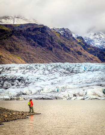 terminus: Hiker on the shore of Fjallsarlon lagoon at a glacier terminus in the south of Iceland Stock Photo