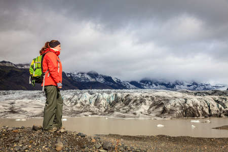 fjallsarlon: Hiker on the shore of Fjallsarlon lagoon at a glacier terminus in the south of Iceland Stock Photo